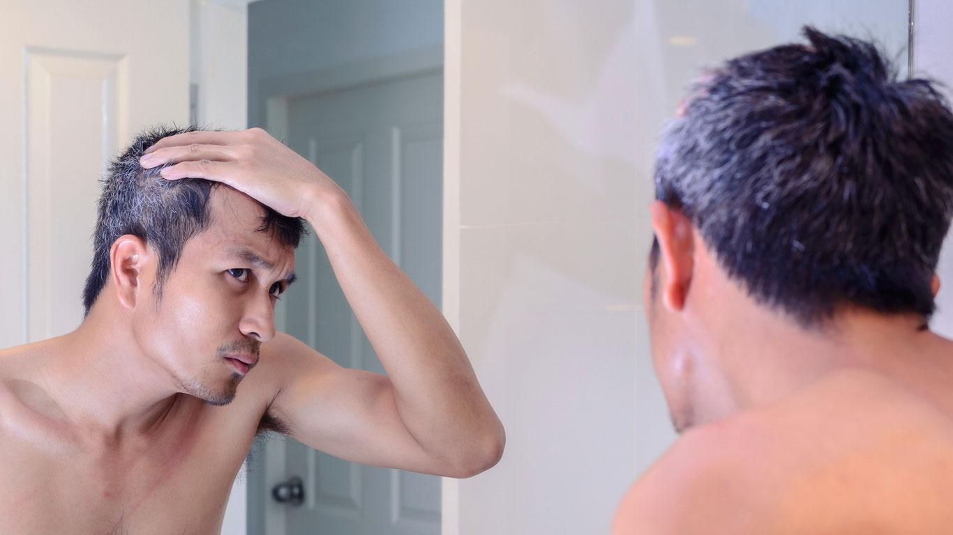 Ergrauter Mann schaut in den Spiegel