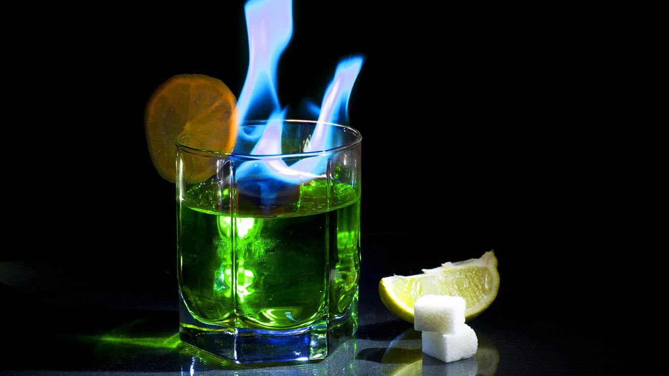 Glas mit Absinth und blauer lodernder Flamme