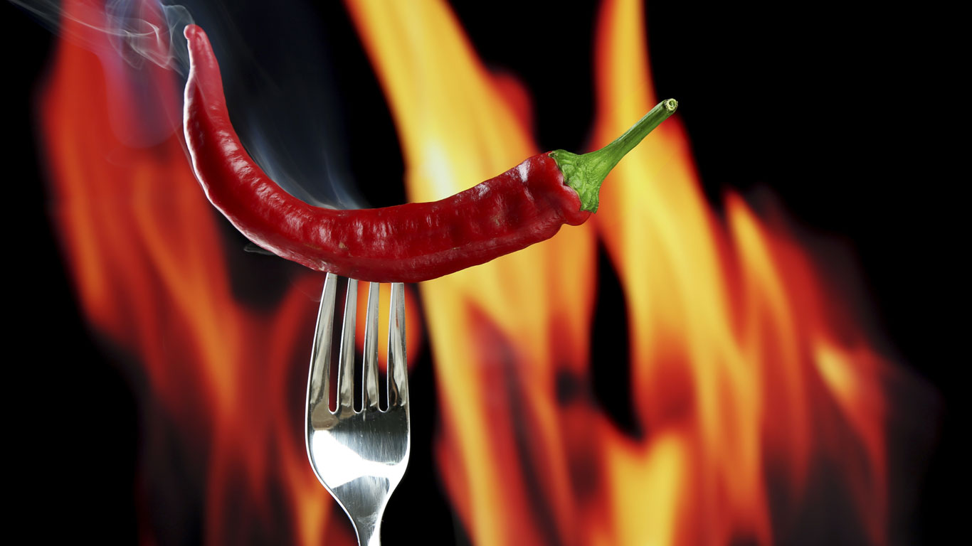 Rote Peperoni auf einer Gabel mit Flammen im Hintergrund